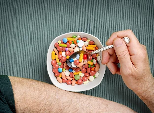 人は夕食のテーブルでスプーンでボウルから丸薬、錠剤、カプセルを食べる