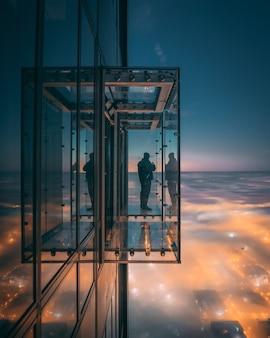 ガラスの壁のバルコニーで街の美しい景色を楽しむ人