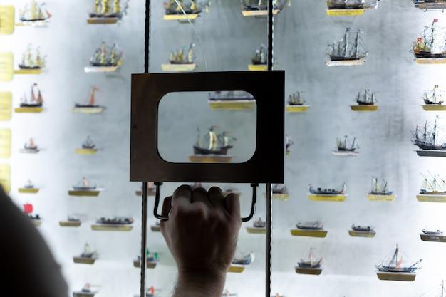 사람은 돋보기를 통해 선박 모델을 검사합니다. 박물관에서 전시입니다.