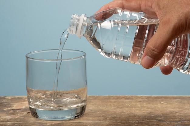 Человек, наполняющий чашку воды бутылкой для домашних животных