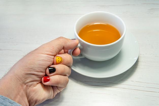 Человек наполняет чашку зеленым чаем в кафе. мужчина с накрашенными ногтями. дизайн мужских ногтей. мужской маникюр.