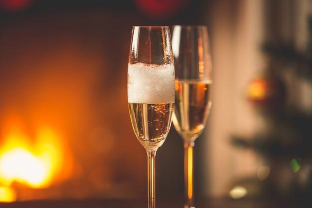 グラス2杯にシャンパンを入れる人。燃える暖炉と飾られたクリスマスツリー
