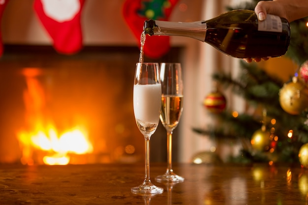 Person filling two glasses with champagne. burning fireplace and decorated christmas tree on the background