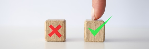 Person finger points to a cube with green check mark. making right decision concept