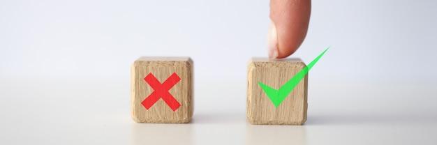 사람의 손가락은 녹색 확인 표시가 있는 큐브를 가리킵니다. 올바른 결정 개념 만들기