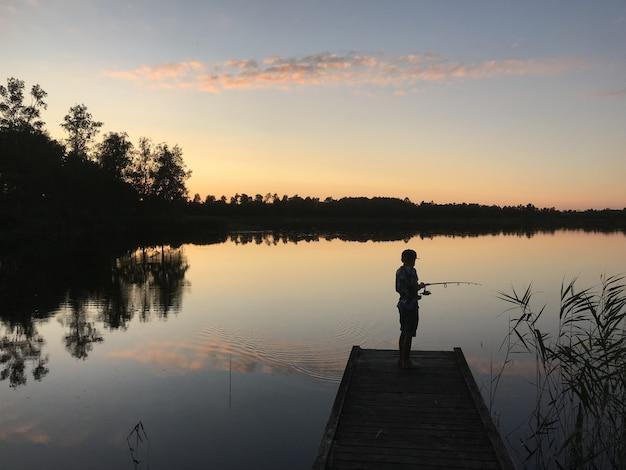 木々に囲まれた湖から釣りをする人