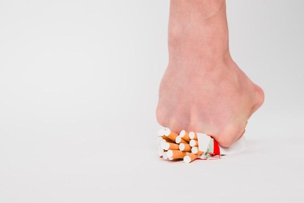 Un pugno di persona che schiaccia pacchetto di sigarette su sfondo bianco