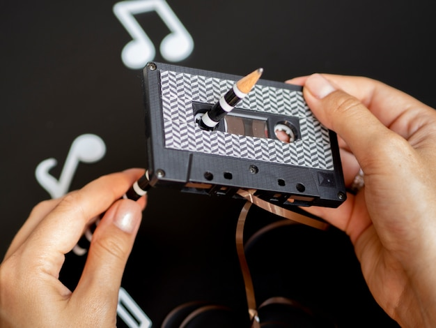Person fixing up cassette tape with modern pattern