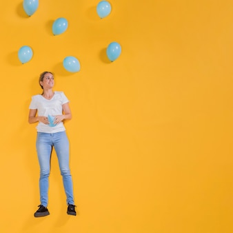 Person floating with blue balloons