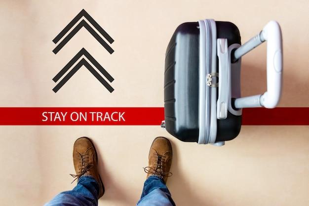검은 색 여행 가방을 들고 바닥에 표시된 방향을 따르는 사람