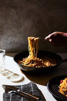 Person getting some spaghetti from a black pot on a white table