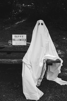 Person in ghost costume sitting on bench near happy halloween inscription