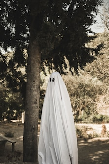 Person in ghost costume standing near tree