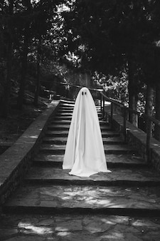 Person in ghost costume standing on stairs in forest