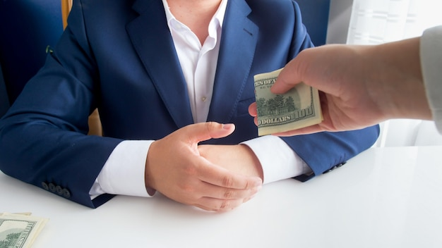 Person giving money bribe to corrupted official or politician