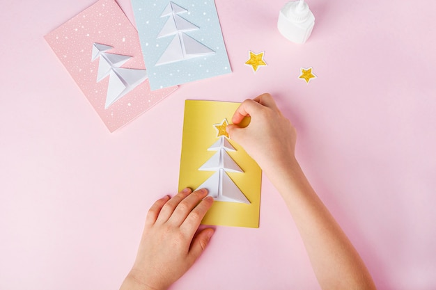Person glueing papers and creating cards with christmas trees