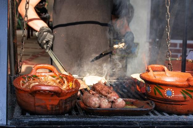 야외에서 그릴에 굽고 있는 사람 바베큐 그릴에 있는 점토 냄비