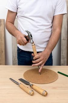 木片を槌で打つ人