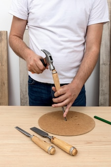 Person hammering a piece of wood