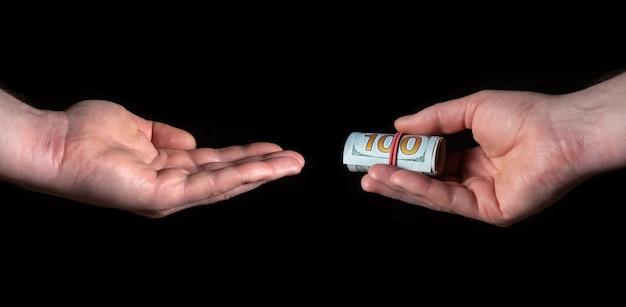 Рука человека дает доллары, а другая рука человека берет их