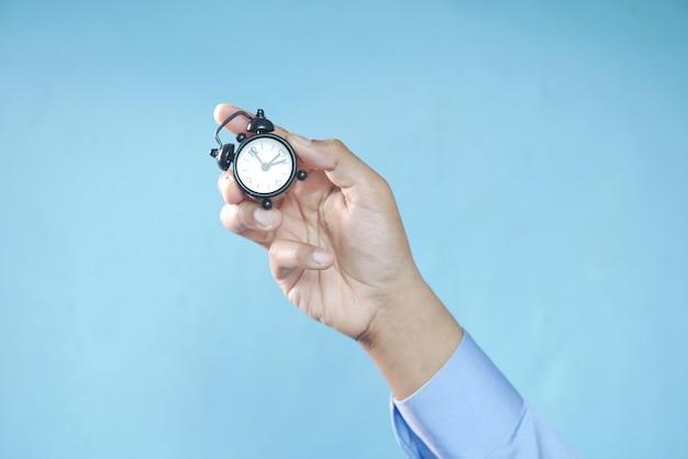 파란색 배경에 알람 시계를 들고 있는 사람 손