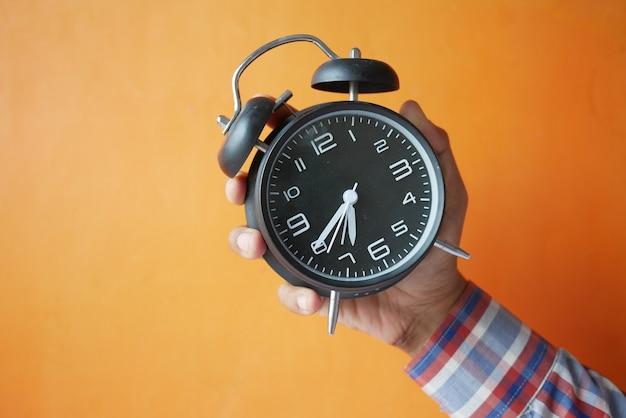 오렌지 배경에 알람 시계를 들고 사람 손