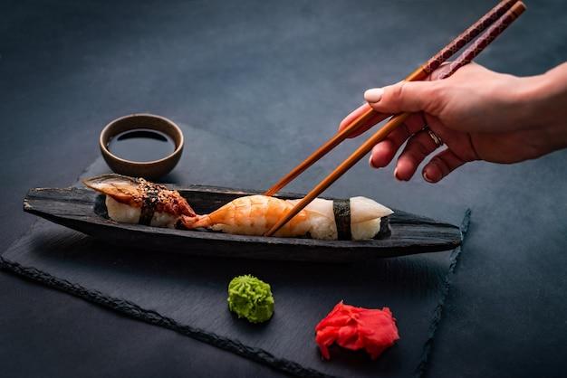 Человек держит палочки для еды и ест суши сашими с креветками, имбирем и соевым соусом, подаваемым с ...