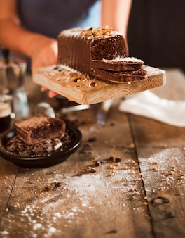 A person hand holding slice of cake on chopping board