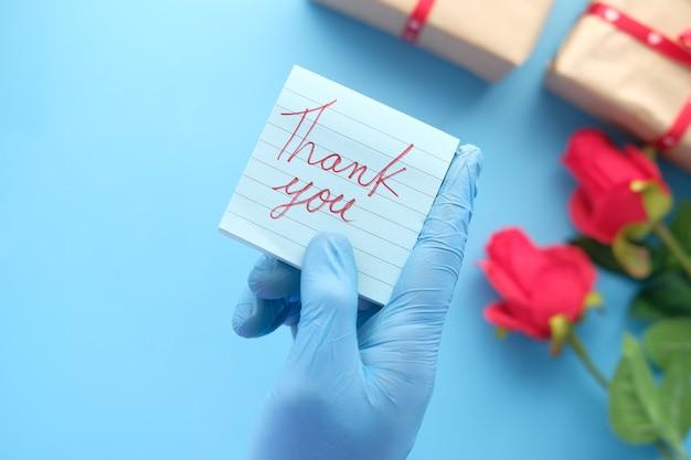 お礼状を持って保護手袋をはめて人の手。