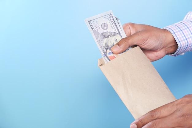 파란색 배경에 봉투에 현금을 넣어 사람 손