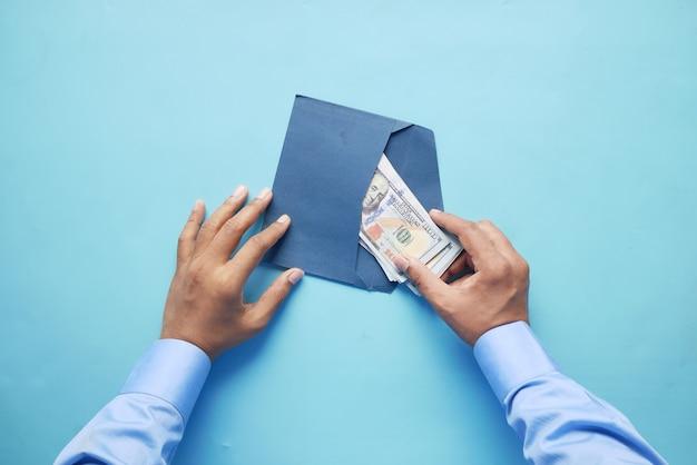 봉투 평면도에 현금을 넣는 사람 손