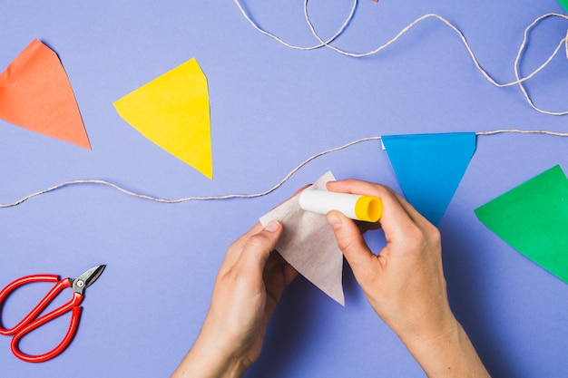 A person hand sticking bunting paper with glue stick