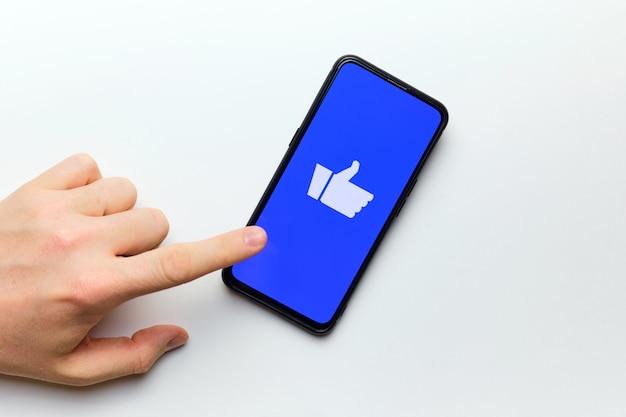 人の手は、スマートフォンを使用してインターネットで評価するために親指を押し上げたいと考えています。