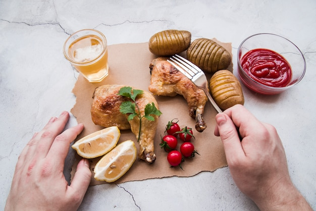 Person hand with fork against roasted chicken with potatoes and beer