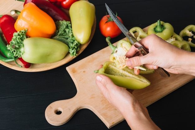 A person' hand with knife holding bell pepper over black kitchen counter