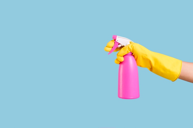 A person hand in yellow glove holding pink spray bottle on blue backdrop