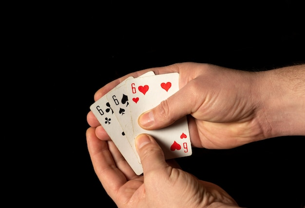 Person hands are holding playing cards three sixes