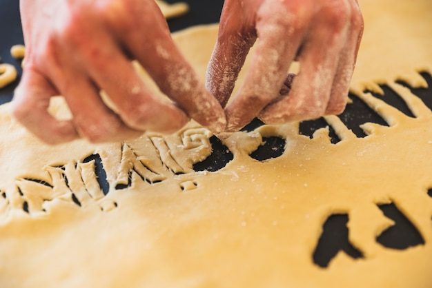 Person handstaking away dough letters