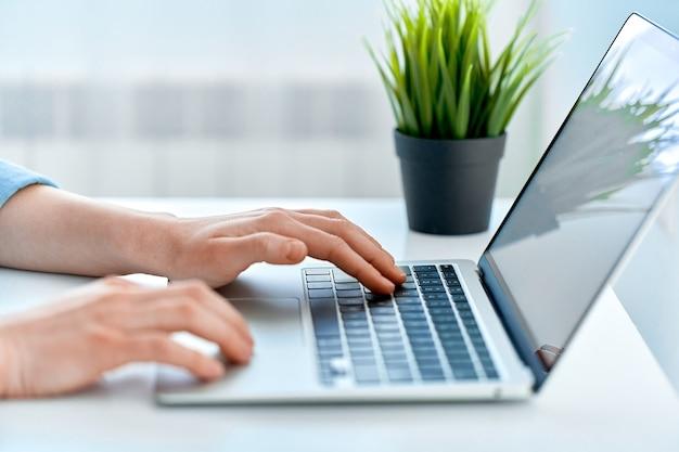 ノートパソコンのキーボードで入力する人の手は、オンラインでスマートに作業しながらクローズアップ