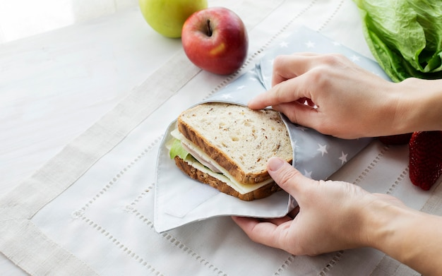 Person hands wrapping whole grain sandwich wrapped in reusable bag zero waste ecologic concept