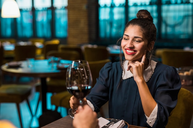 Person and happy woman clanging glasses of wine at table in cafe