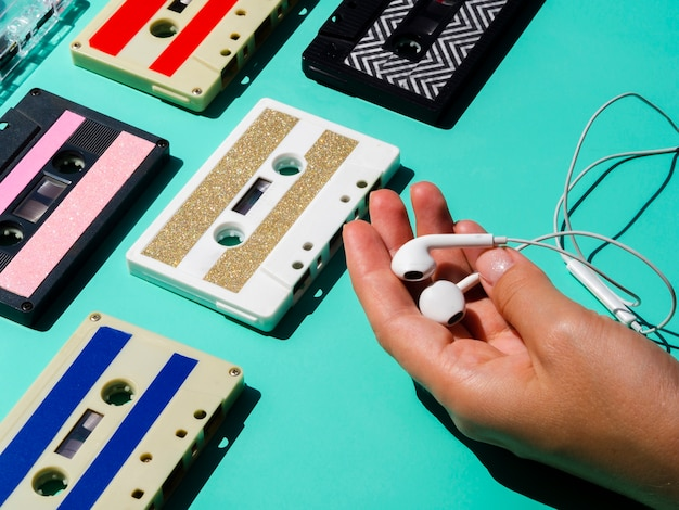 Person holdig headphones near cassette tape collection