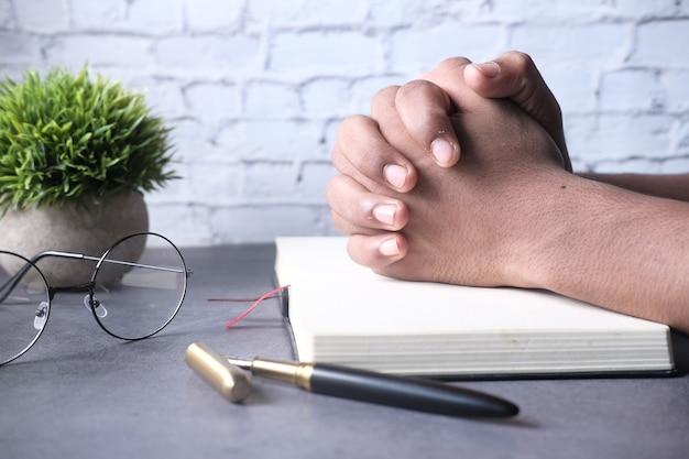 Человек держит библию в руках и молится.