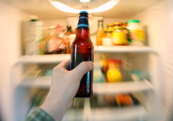 Person holding a bottle of beer in front of open refrigerator