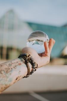 三角形の建物の反射で透明なクリスタルガラスのボールを持っている人