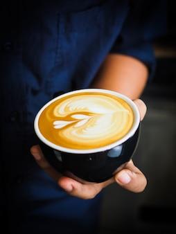 한 잔의 커피를 들고있는 사람