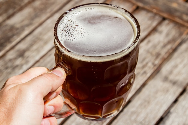 木製の表面と冷たいビールのグラスを持っている人