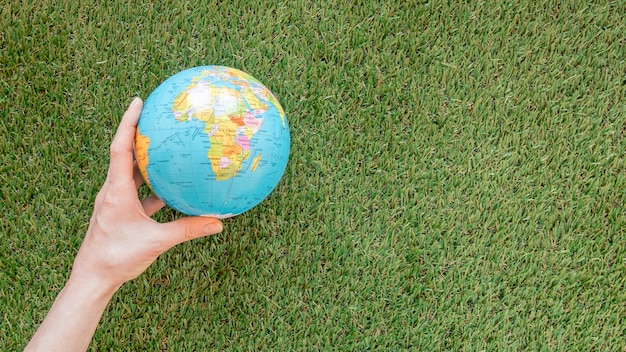 Человек держит глобус на траве с копией пространства