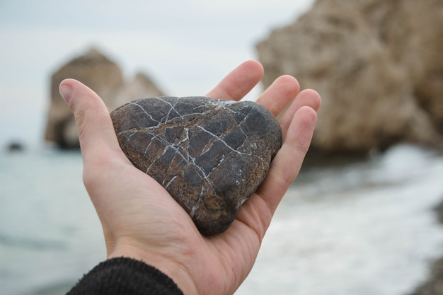 ビーチでハート型の岩を手に持っている人