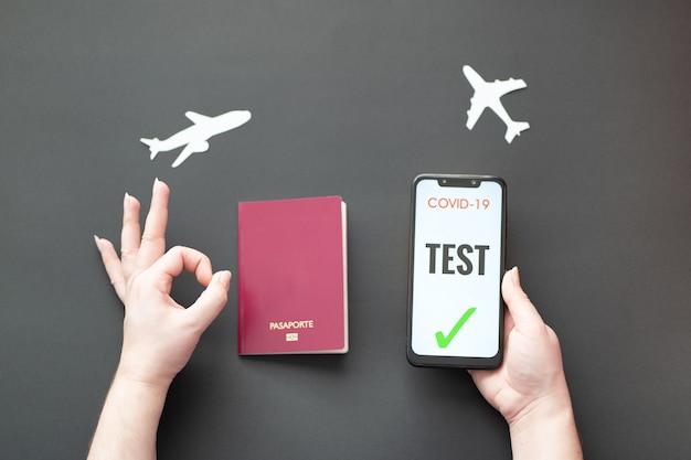 비행기와 검은 배경에 covid 테스트와 여권과 스마트 폰을 들고 사람